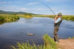 Fisherman catches of salmon Stock Photos