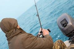 Fisherman catches a salmon Stock Photos