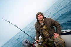 Fisherman catches a salmon in the sea stock photography