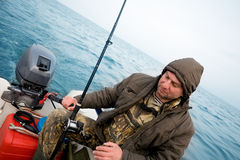 Fisherman catches a salmon in the sea stock photo