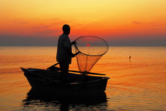 The fisherman catches the sun. Stock Photography