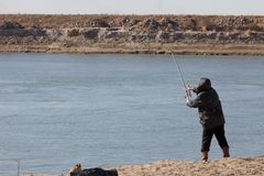 Fisherman catching a fish on a fishing tackle in the river Royalty Free Stock Images