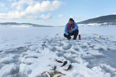 Fisherman catching fish on a frozen lake on the snow. Ice fishing. Horizontal. stock image