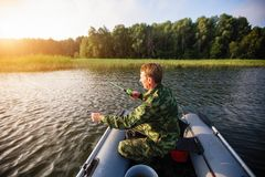 Fisherman catching fish on the river from rubber boat. Hobby. Royalty Free Stock Photography