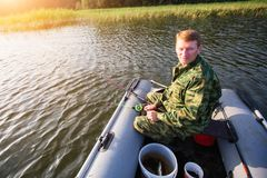 Fisherman catching fish on the river from rubber boat. Nature. Stock Photography