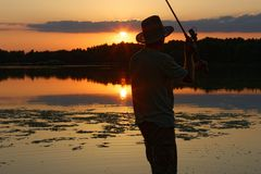 Fisherman. Catching the fish during sunset Stock Photo