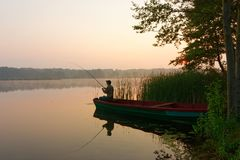 Fisherman. Catching the fish from wooden boat during sunrise Stock Photography