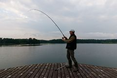 Fisherman. Catching the fish from wooden pier during cloudy day Royalty Free Stock Photography