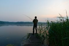 Fisherman. Catching the fish from wooden pier during dawn Royalty Free Stock Photo