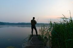 Fisherman. Catching the fish from wooden pier during dawn Stock Images