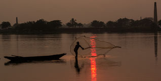 Fisherman catching fishes. Alone fisherman catching fishes in a river at sunset Royalty Free Stock Photo