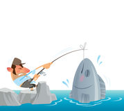 Fisherman catching and pulling out of the sea a big fish Royalty Free Stock Images