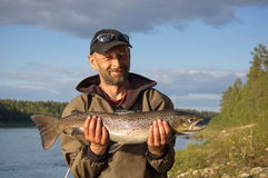 Fisherman caught a big salmon. Royalty Free Stock Photos