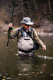 Fisherman caught grayling and pulls him out of river Stock Photos