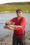 Fisherman caught a large grayling. Royalty Free Stock Image