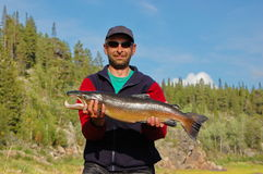 Fisherman caught a nice male salmon in the north river. Varzuga river, Kola Peninsula, Russia Royalty Free Stock Photo