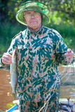 A fisherman caught a pike Royalty Free Stock Photos