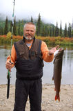 Fisherman caught a small taimen. royalty free stock images