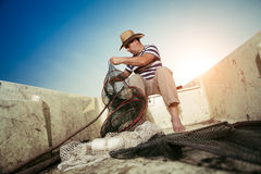 Fisherman checking the net for a catch Stock Images