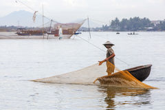 Fisherman checks his nets in early morning on river in Hoian, Vietnam Royalty Free Stock Image