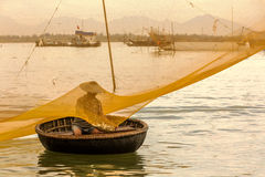 Fisherman checks his nets in early morning on river in Hoian, Vietnam Stock Photography