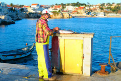 Fisherman cleaning fish Stock Photography