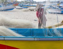 Fisherman cleaning nets. Over a traditional fishing vessel Royalty Free Stock Photo