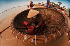 Fisherman cleaning out his fishing basket on the beach. Fisherman cleaning out his round made out of wood brown colored fishing basket with his gloved hands on Royalty Free Stock Image
