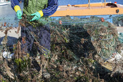Repairing fishing nets. Fisherman cleaning and repairing the fishing net Stock Photo