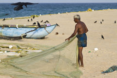 Fisherman cleans net after fishing in Sri Lanka Royalty Free Stock Images