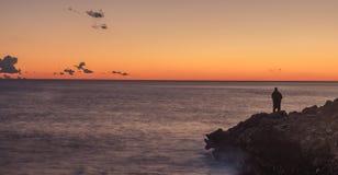 Fisherman on the coast. Nerja, Malaga, Andalusi, Spain - January 21, 2019: A lone fisherman on the coast, with twilight on a sunset of reddish horizon stock photography