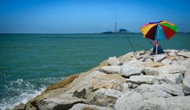 Fisherman and colourful umbrella on rock coast Royalty Free Stock Photo
