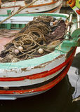 Fisherman complected net on small wooden boat Stock Image