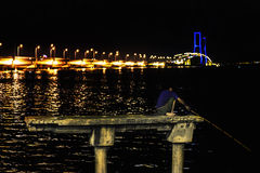 Fisherman on a concrete pylon catch fish at night. In backround Suramadu Bridge at Twilight,Surabaya,Indonesia.Is the longest. Fisherman on a concrete pylon stock images