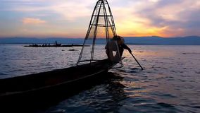 The fisherman with conical net, Inle Lake, Myanmar. The art of sunset fishing on Inle Lake - Burmese fisherman shows his skills of one leg paddling and fishing stock video footage