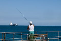 Fisherman and container ship Royalty Free Stock Photos