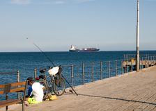 Fisherman and container ship Stock Photos