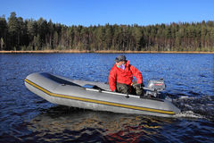 Fisherman controls gray inflatable rubber boat with an outboard Stock Image