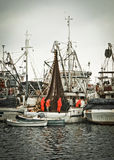 Fisherman crew fixing nets on fishing boat Royalty Free Stock Image