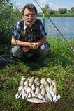 Fisherman with crucian on river Chagan Royalty Free Stock Images