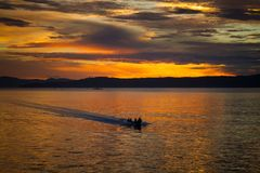 The fisherman are cruising to the ocean for fishing on beautiful sunrise. The fisherman are cruising to the ocean for fishing on beautiful golden sunrise stock photos