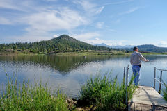 Fisherman on dock near mountain lake in Colorado. A fisherman fishes on dock at Lake Hatcher, Pagosa Springs Colorado on a beautiful sunny summer day Stock Photo