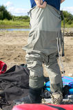 Fisherman donning a pair of waders Royalty Free Stock Photography