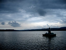 Fisherman on Dramatic Lake. A storm is breeding in the air. The last glimpses of the sun penetrate the thin layer of clouds from the far horizon. The rest of the Royalty Free Stock Photography