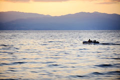 Fisherman driving a boat on Ohrid Lake at sunset Royalty Free Stock Photo
