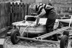 Fisherman empties his boat of water. Yorkshire fisherman in overalls gets his boat ready for sea Royalty Free Stock Images