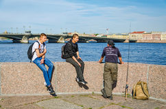 A fisherman at the English embankment and his spectators. Saint Petersburg, Russia, July 26, 2015. A fisherman at the English embankment and his spectators Royalty Free Stock Photo