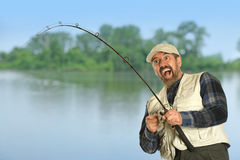 Fisherman Expressing Joy after Catching Fish. Happy Hispanic fisherman catching fish with rod stock photos