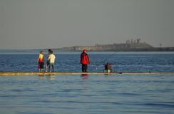 Fisherman and family on harbor Stock Photography