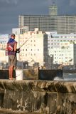 Fisherman at the famous Malecon seawall in Havana. HAVANA,CUBA - NOVEMBER 25,2017 : Fisherman at the famous Malecon seawall in Havana with a view of the city Royalty Free Stock Photography